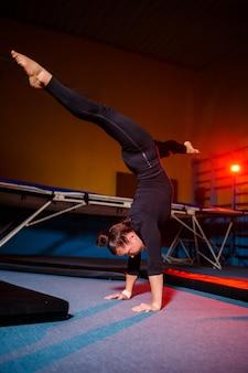 Jong sportief meisje die handstandoefening doen. jonge vrouw doet touw terwijl ze op handen staat