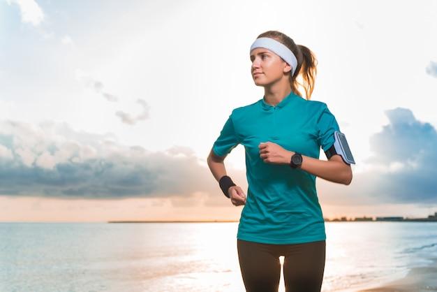 Jong sportief meisje die op strand bij zonsopgang in ochtend lopen