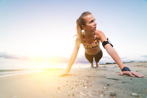 Jong sportief meisje die plankoefening op strand doen bij zonsopgang