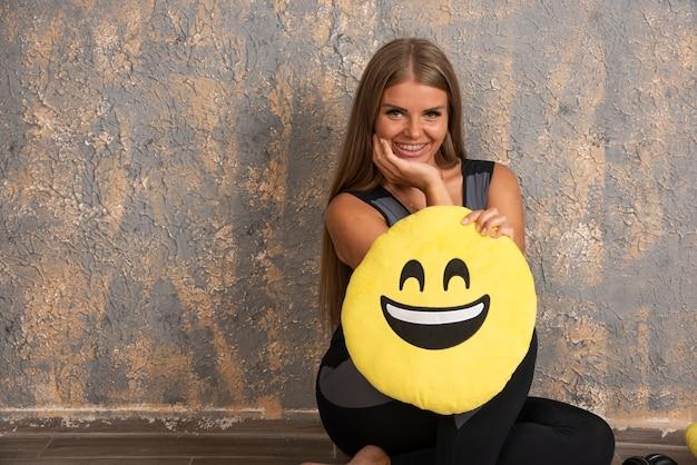 Jong sportief meisje in sportoutfits die een glimlachend emoji-hoofdkussen houden.