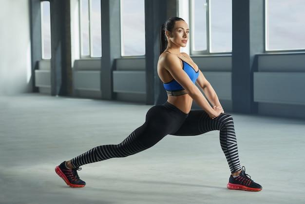 Jong sportief meisje met atletisch lichaam die fallouts in gymnastiek doen