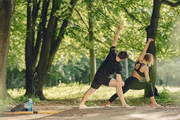 Jong sportief paar dat yogageschiktheid doet. mensen in een zomerpark.