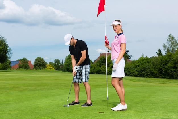 Jong sportief paar speelgolf op een cursus