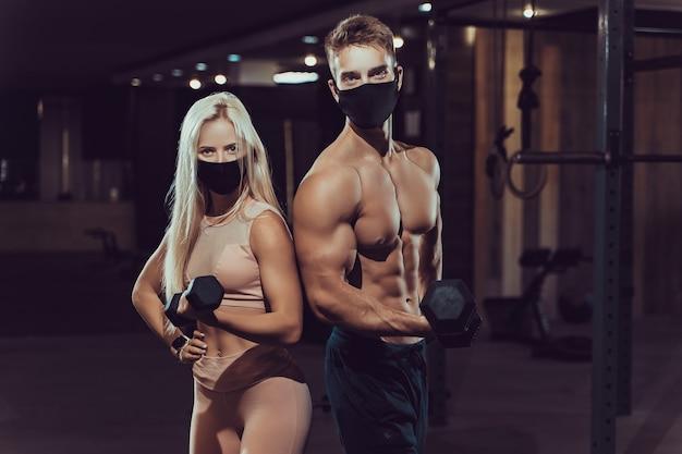 Jong sportief sexy stel in maskers van covid-19 die spier- en training in de sportschool tonen. gespierde man en vrouw.