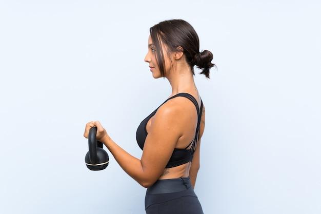 Jong sportmeisje die gewichtheffen met kettlebell over geïsoleerde blauwe muur maken