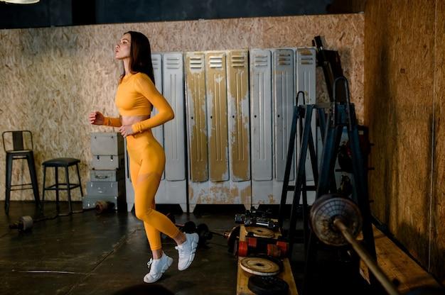 Jong sportmeisje in een geel sportuniform maak je klaar voor een moderne loft-gymnastiek