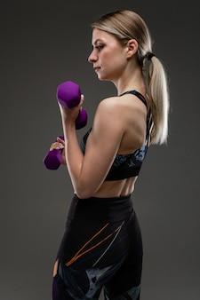 Jong sportmeisje met lang blond haar gevuld in staart, mooi uiterlijk, sportlichaam, in zwarte top en legines, houdt paarse rubberen gants in haar handen