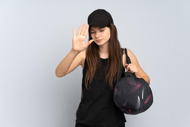 Jong sportmeisje met sporttas dat op grijs wordt geïsoleerd dat stopgebaar maakt en teleurgesteld