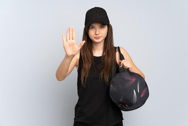 Jong sportmeisje met sporttas dat op grijs wordt geïsoleerd dat stopgebaar maakt