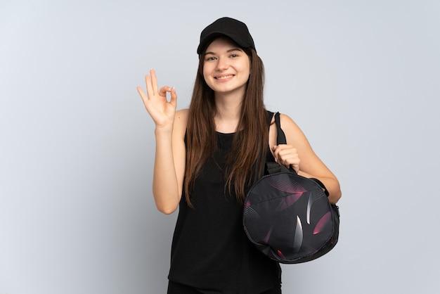 Jong sportmeisje met sporttas dat op grijs wordt geïsoleerdg ok teken met vingers tonen