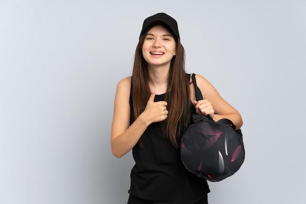 Jong sportmeisje met sporttas geïsoleerd op grijs met een duim omhoog gebaar