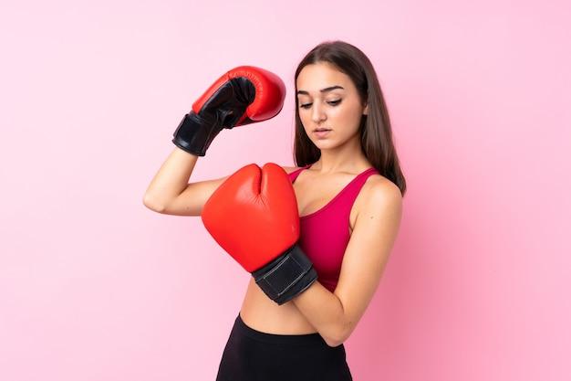 Jong sportmeisje over geïsoleerd roze met bokshandschoenen