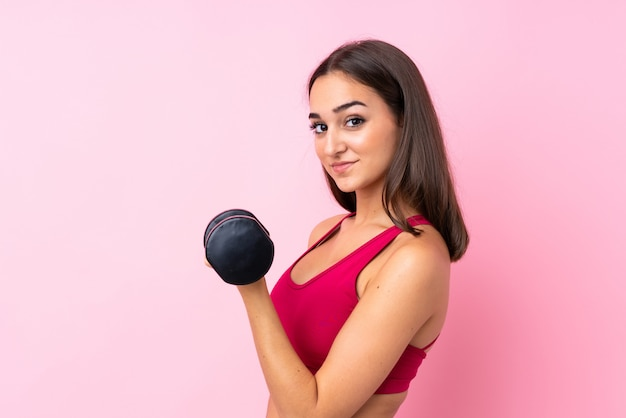Jong sportmeisje over geïsoleerde roze achtergrond die gewichtheffen maakt