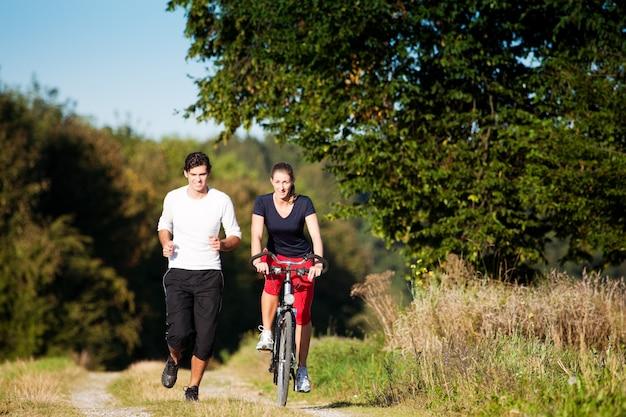 Jong sportpaar joggen en fietsen