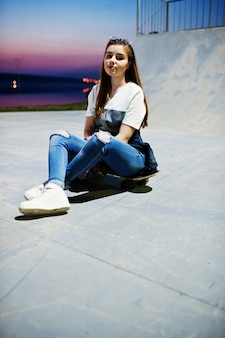 Jong stedelijk tienermeisje met skateboard, slijtage op glazen, pet en gescheurde jeans bij skatepark op de avond.