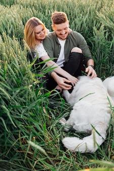 Jong stel aait hun hond tijdens het wandelen in de velden op zomeravond. liefde en tederheid. mooie momenten van het leven. jeugd en schoonheid. rust en zorgeloosheid. wandelen in de natuur. levensstijl.