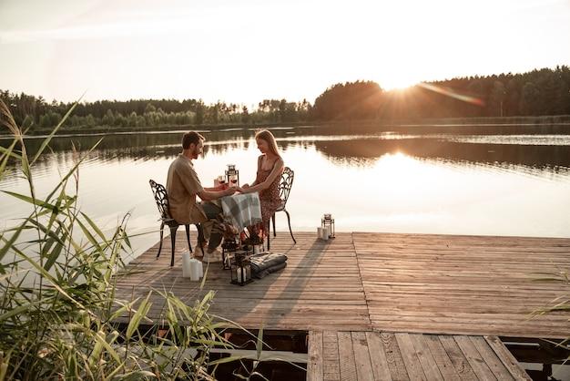 Jong stel brengt samen tijd door met het drinken van wijn op houten pier: knappe man houdt de hand van zijn vriendin vast, doet huwelijksaanzoek tijdens zonsondergang, draagt verlovingsring, bosmeerachtergrond