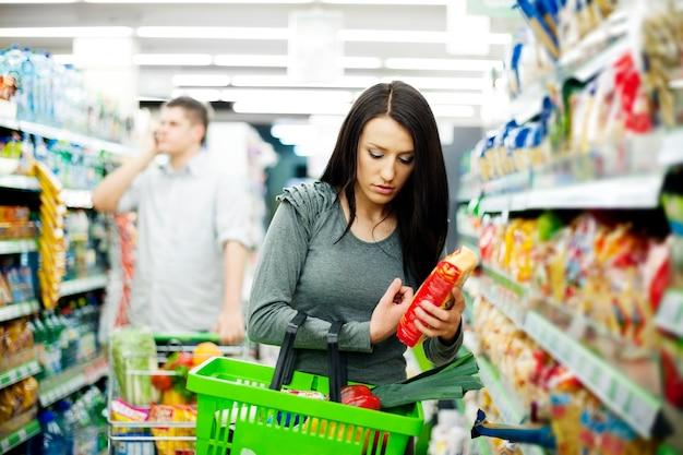 Jong stel dat bij supermarkt winkelt