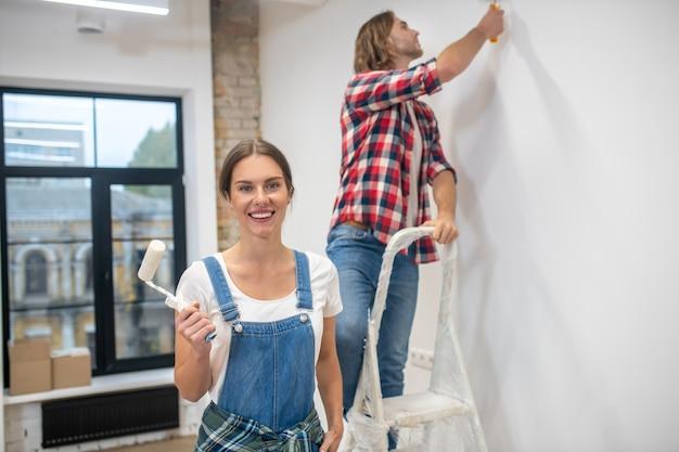 Jong stel dat een muur schildert en zich goed voelt