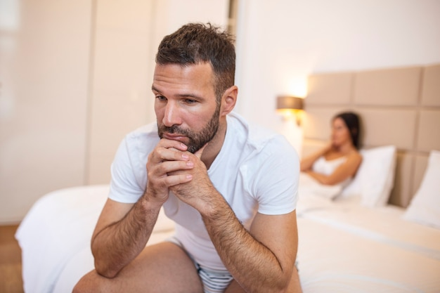Jong stel dat een probleem heeft. guy zit op bed en kijkt droevig weg, zijn vriendin op de achtergrond.