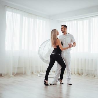 Jong stel dat latinmuziek danst: bachata, merengue, salsa. elegantie twee stelt op witte ruimte