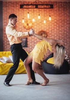 Jong stel dat latinmuziek danst: bachata, merengue, salsa. twee elegantie vormen op café met bakstenen muren
