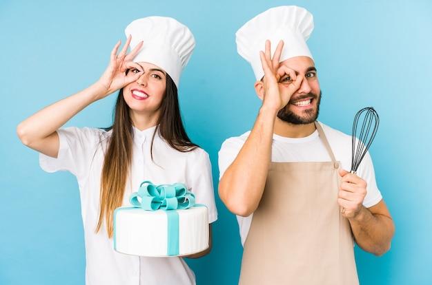 Jong stel dat samen een cake kookt geïsoleerd opgewonden houdend ok gebaar op oog.