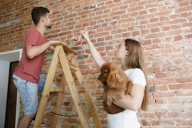 Jong stel dat zelf appartementreparatie doet. getrouwde man en vrouw die huis make-over of renovatie doen. concept van relaties, familie, huisdier, liefde. bespreek het toekomstige ontwerp aan de muur.