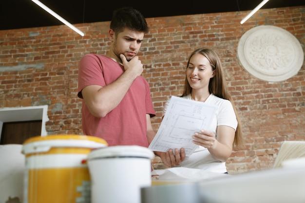 Jong stel dat zelf appartementreparatie doet. getrouwde man en vrouw die huis make-over of renovatie doen. concept van relaties, familie, liefde. bespreek het ontwerp van de muur met een notitieboekje.