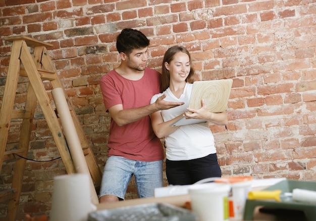 Jong stel dat zelf appartementreparatie doet. getrouwde man en vrouw die huis make-over of renovatie doen. concept van relaties, familie, liefde. het ontwerp van de muur kiezen met een notitieboekje.