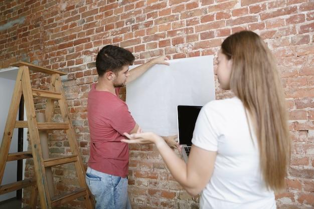 Jong stel dat zelf appartementreparatie doet. getrouwde man en vrouw die huis make-over of renovatie doen. concept van relaties, familie, liefde. het ontwerp van de muur maken met een notitieboekje.