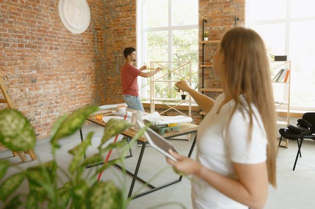 Jong stel dat zelf appartementreparatie doet. getrouwde man en vrouw die huis make-over of renovatie doen. concept van relaties, familie, liefde. het voltooide ontwerp controleren, nieuwe meubels plaatsen.