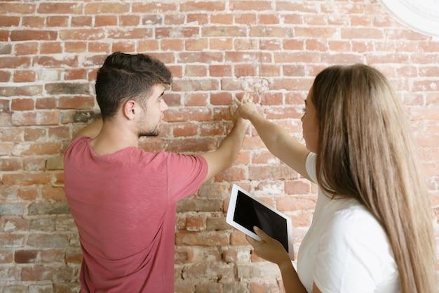 Jong stel dat zelf appartementreparatie doet. getrouwde man en vrouw die huis make-over of renovatie doen. concept van relaties, familie, liefde. meet en bespreek het toekomstige ontwerp aan de muur. Gratis Foto
