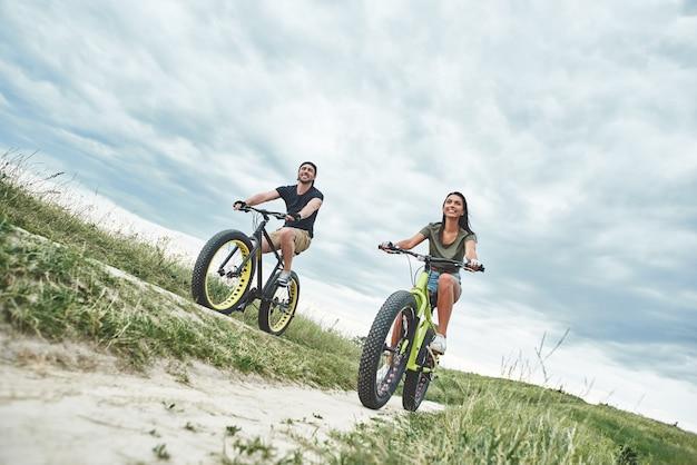 Jong stel fietst op de bodem van de groene heuvels
