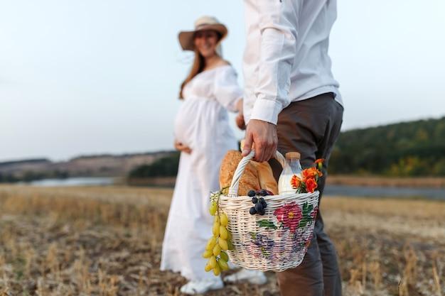 Jong stel gaat picknicken in het veld, de man draagt een mand met fruit, melk en brood