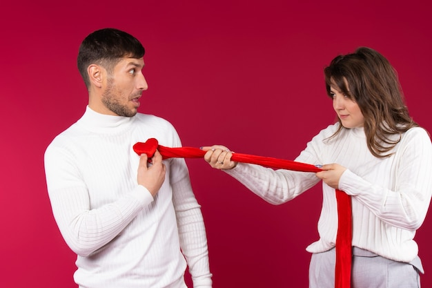 Jong stel gek rond. het meisje scheurt een denkbeeldig hart uit de borst van de man. rode achtergrond. valentijnsdag.