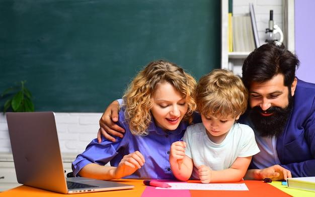 Jong stel helpt zijn zoon om huiswerk te maken begin van lessen onderwijs voor kinderen uit