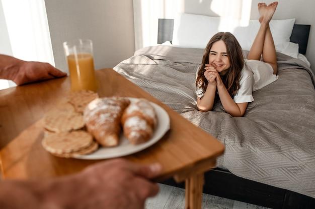 Jong stel in bed. de glimlachende mooie hongerige vrouw wacht op heerlijk ontbijt in de ochtend