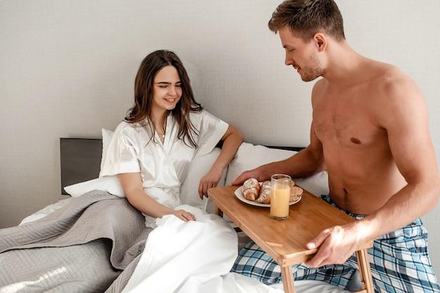 Jong stel in bed. mooie man houdt de tafel met heerlijk ontbijt voor zijn geliefde