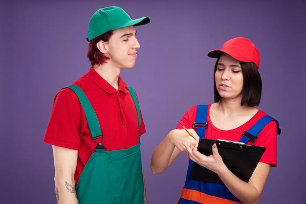Jong stel in bouwvakkeruniform en pet serieus meisje met potlood en klembord naar beneden te kijken en uitleg te geven over iets blije man die naar haar kijkt