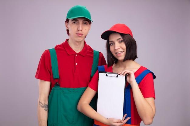 Jong stel in bouwvakkeruniform en pet serieuze man glimlachend meisje beide meisje met klembord