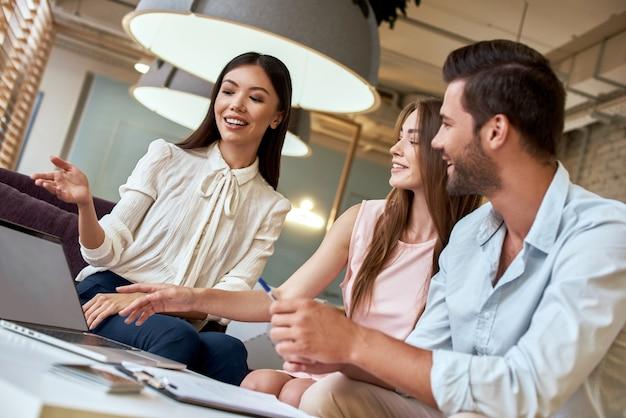 Jong stel in een reisbureau luistert voorstel van reisbureau