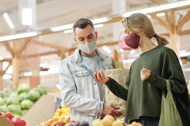 Jong stel in maskers die aan de balie staan en samen fruit controleren voordat ze kopen