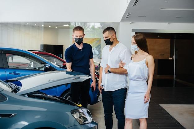 Jong stel in maskers kiest een nieuw voertuig en overlegt met een vertegenwoordiger van de dealer in de periode van de pandemie. autoverkoop en het leven tijdens de pandemie.