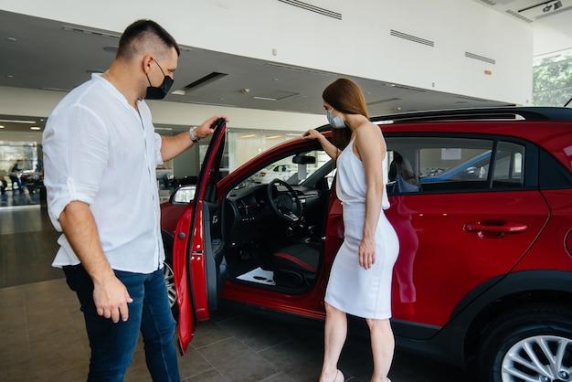 Jong stel in maskers kiest een nieuw voertuig en overlegt met een vertegenwoordiger van de dealer in de periode van de pandemie