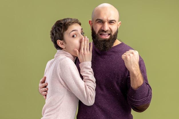 Jong stel in vrijetijdskleding bebaarde man balde vuist terwijl zijn vriendin hem een geheim vertelt valentijnsdag vieren staande over groene muur