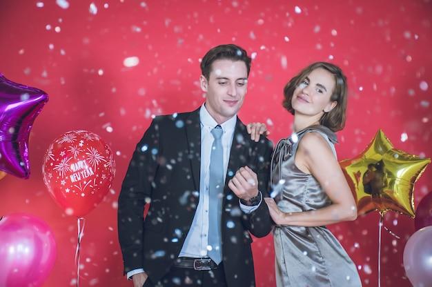 Jong stel is gelukkig onder de confetti die vooraan valt. er zijn kleurrijke ballonnen naast hen en de rode muur in het concept van nieuwjaar en eerste kerstdag.