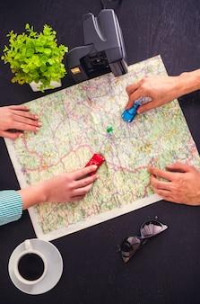 Jong stel kiest een plaats om te reizen met behulp van de kaart.