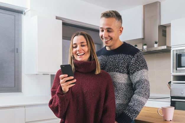 Jong stel, man en vrouw die een geweldige tijd hebben samen op zoek naar een mobiele telefoon in de keuken