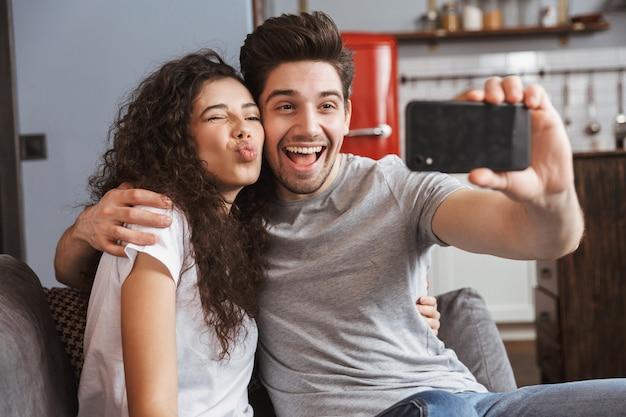 Jong stel man en vrouw die thuis op de bank zitten en samen selfie-foto maken op smartphone